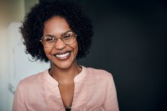 Laughing African businesswoman standing alone in a modern office. Young African businesswoman wearing glasses and laughing while standing alone in a modern stock photography