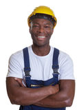 Laughing african construction worker with crossed arms Stock Photos