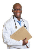 Laughing african doctor with a medical record in his hand stock photography