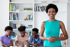Laughing african female teacher with class at school. Laughing african female teacher looking at camera with class at school royalty free stock image