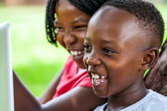 Laughing African kids looking at laptop screen. Close up face shot of African kids laughing at movie scene on digital tablet outdoors royalty free stock photography