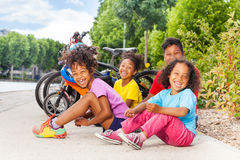Laughing African kids sitting on the bike path. Group of African children sitting on the bike path after cycling in summer park royalty free stock images