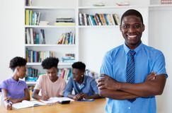 Laughing african male teacher with class at school. Laughing african male teacher looking at camera with class at school stock photography