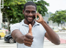 Laughing african man with beard at phone showing thumb up stock photos
