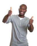 Laughing african man showing both thumbs Stock Photo