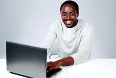 Laughing african man sitting at the table Royalty Free Stock Photos