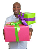 Laughing african man with two gifts for christmas Royalty Free Stock Image