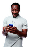 Laughing african man using smartphone Royalty Free Stock Images