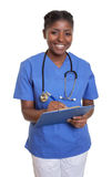 Laughing african nurse with clipboard Royalty Free Stock Image