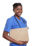 Laughing african nurse with file of a patient Stock Image