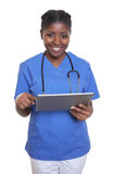 Laughing african nurse working with tablet computer royalty free stock images