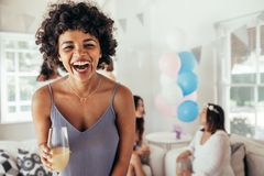 Laughing african woman at friend`s baby shower. Laughing african young women holding a glass of juice with friends in background at baby shower party. Female Stock Photo