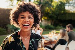 African woman enjoying at outdoors party. Laughing african women with friends sitting in background at party. African women enjoying at outdoors party royalty free stock photography