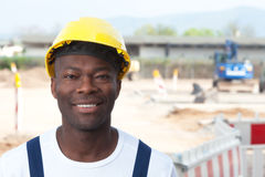 Laughing african worker at construction zone looking at camera Royalty Free Stock Images
