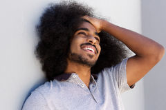 Laughing afro man with hand in hair looking away. Close up portrait of laughing afro man with hand in hair looking away Royalty Free Stock Photo