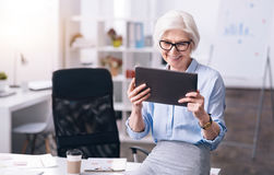 Laughing aged woman enjoying her job in the office royalty free stock images