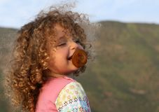 Laughing angelic curly little girl with soother Stock Photography