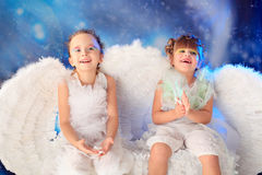 Laughing angels. Beautiful little angels at a snowy background Royalty Free Stock Photography