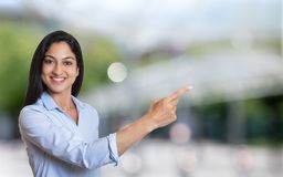 Laughing arabic businesswoman pointing sideways. Outdoor in front of an office building Stock Photography