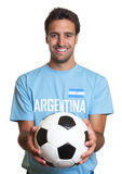 Laughing argentinian man with football. Argentinian man with football laughing at camera because he is happy about his national team on an isolated white Stock Image