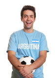 Laughing argentinian soccer fan with ball. On an isolated white background for cutout Stock Images