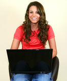 Laughing as she works. A pretty teenage girl works on her laptop royalty free stock photo