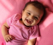 Laughing asian baby girl in pink cloths. Laughing and playful asian (Indian) baby girl in pink cloths and pink background. Baby is three month old Stock Photos