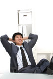 Laughing Asian businessman with his feet up Stock Photography