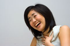 Laughing Asian woman. Beautiful Asian Chinese Japanese woman in a white collared shirt laughing, isolated Royalty Free Stock Image