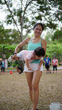 Laughing Asian woman carrying toddler and participating in family games outdoor Stock Images