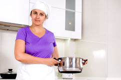 Laughing attractive cook with a big pot Stock Images