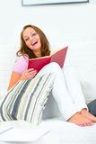 Laughing attractive woman with book on couch Stock Photo