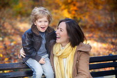 Laughing in autumn. Happy little boy and his mother laughing and having fun in nature in autumn Royalty Free Stock Image