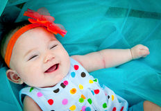 Laughing Baby. A beautiful baby surrounded by blue laughing for the camera Royalty Free Stock Photos