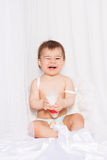 Laughing baby with angel wings sitting Stock Photos
