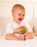 Laughing baby and apple Royalty Free Stock Image