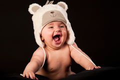 Laughing baby in bear cap. In black background Stock Photo
