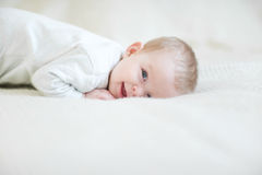 Laughing baby on bed Stock Photography