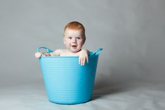Laughing baby in a blue bucket Royalty Free Stock Photos