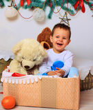 Laughing baby in the box with a bear Stock Photos