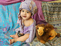 Laughing baby boy dressing in turban sits on Asian fabrics Royalty Free Stock Photo