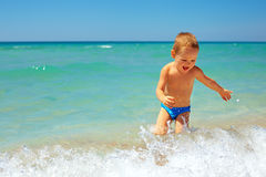 Laughing baby boy having fun in sea Stock Images