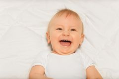 Laughing baby boy in white bodysuit lay on blanket Stock Photography