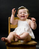 Laughing baby in chair Royalty Free Stock Image