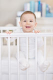 The laughing baby in a cot at home - baby in bed Royalty Free Stock Photo