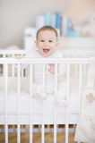 The laughing baby in a cot at home - baby in bed Royalty Free Stock Photos