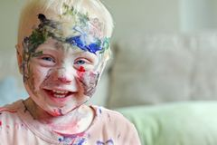 Laughing Baby Covered in Paint. A cute baby boy is laughing after he has covered his entire face in rainbow colored paint royalty free stock photo