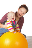 Laughing baby doing exercises. Laughing baby with delayed motor activity development doing exercises with the support of its mother and a yellow gym ball to Stock Image