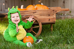 Laughing baby in dragon Halloween costume royalty free stock photo