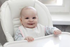 Laughing baby eating in highchair Royalty Free Stock Images